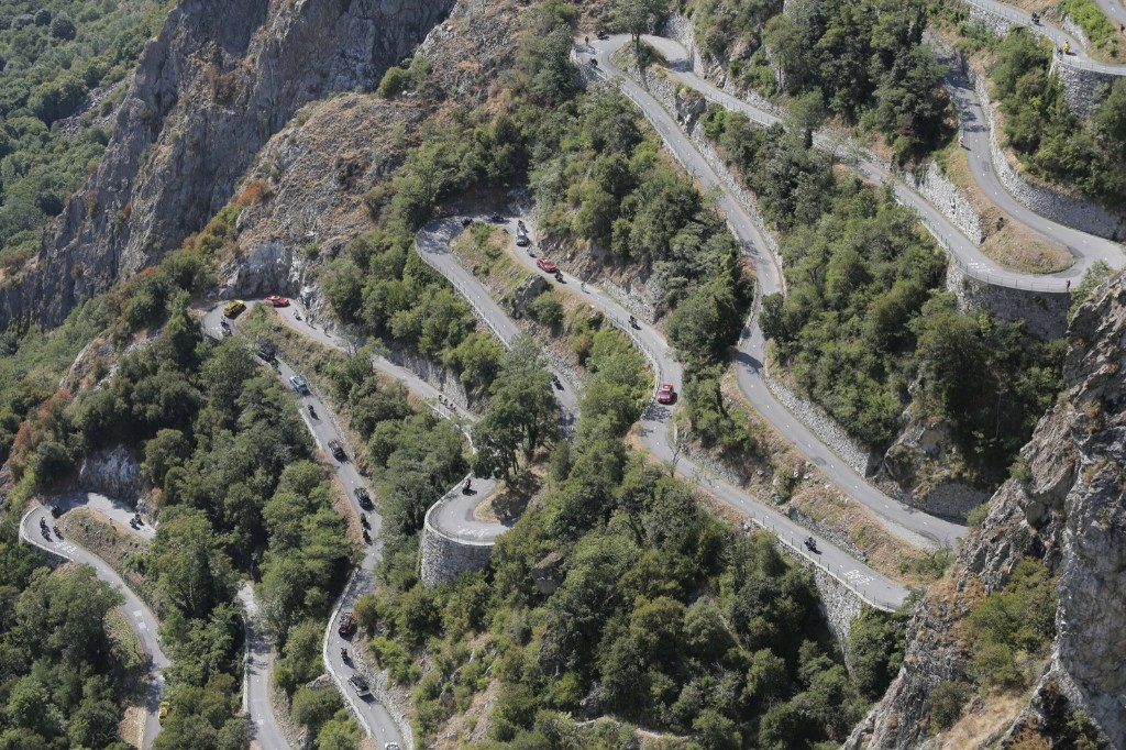 Riders, team cars and press motorcycles climb the harpins of Montvernier during the eighteenth stage of the Tour de France. AP Photo/Laurent Cipriani