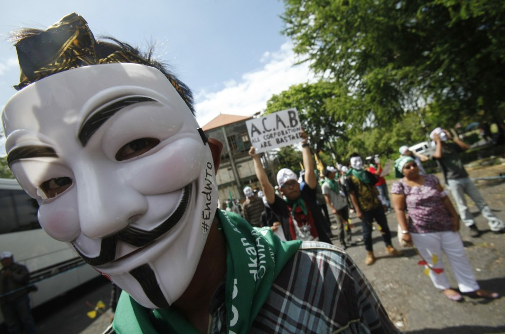 A protester from the Youth Movement of Indonesia Caravan wearing a Guy Fawkes mask gets ready to take to the streets ahead of the ninth World Trade Organization Conference. REUTERS/Edgar Su