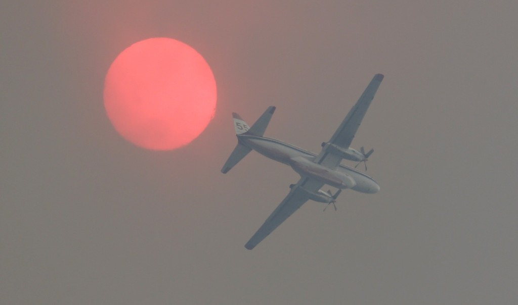 A fire-retardant airplane passes near the sun as a wildfire burns near Twisp, Wash. AP Photo/Ted S. Warren