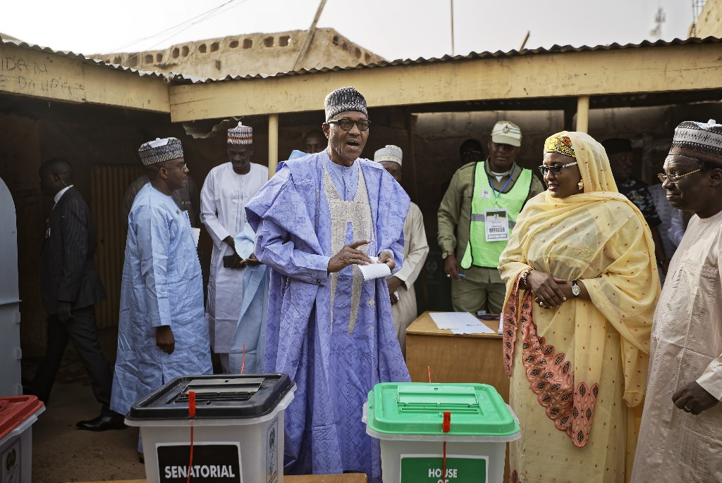 Nigeria's President Muhammadu Buhari casts his vote, accompanied by his wife Aisha, right, in his hometown of Daura, in northern Nigeria Saturday, Feb. 23, 2019. Nigerians are going to the polls for a presidential election Saturday, one week after a surprise delay for Africa's largest democracy. (AP Photo/Ben Curtis)