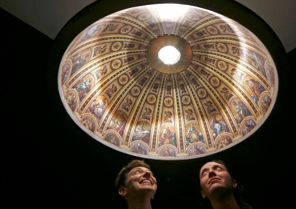 Italian designers Eleonora Barbareschi (L) and Alessandra Mantovani under their suspended lamp with a hyper-realistic reproduction of Saint Peter Basilica's dome at Milan Design Week. REUTERS/Stefano Rellandini