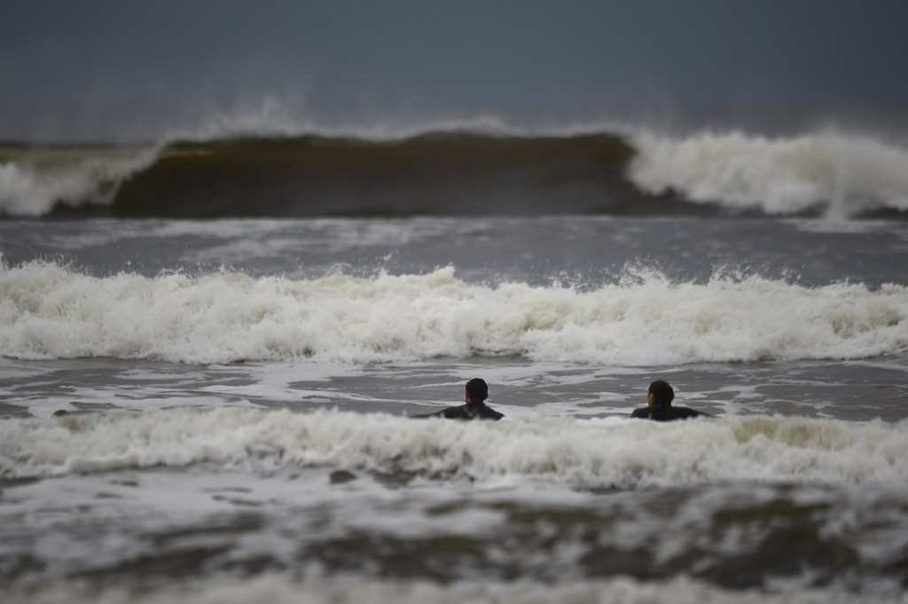 Surfers watch as waves approach in the Atlantic on the eve of storm Ophelia in an area where the tide should be out in the County Clare town of Lahinch, Ireland. REUTERS/Clodagh Kilcoyne
