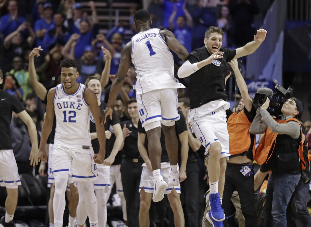 Duke players including Javin DeLaurier (12) and Zion Williamson (1) celebrate after defeating Florida State in the NCAA college basketball championship game of the Atlantic Coast Conference tournament in Charlotte, N.C., Saturday, March 16, 2019. (AP Photo/Chuck Burton)