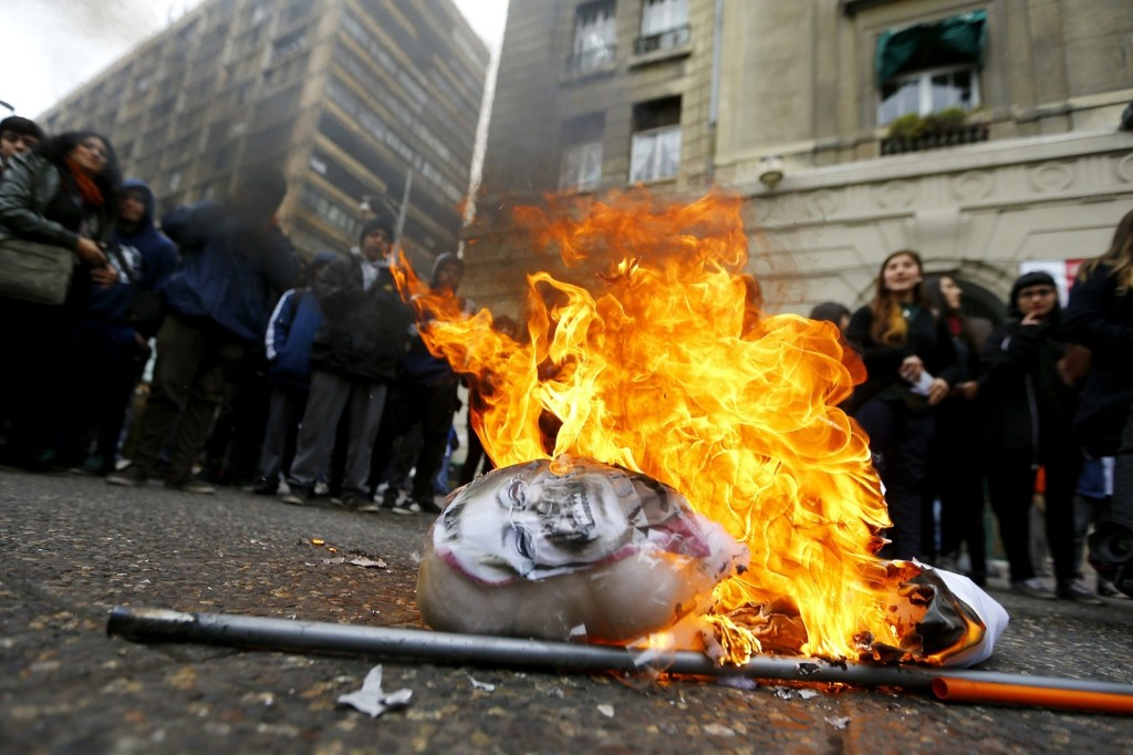 High school students gather around a burning effigy of Chile's President Michelle Bachelet during rally in front of Santiago's town hall. REUTERS/Ivan Alvarado