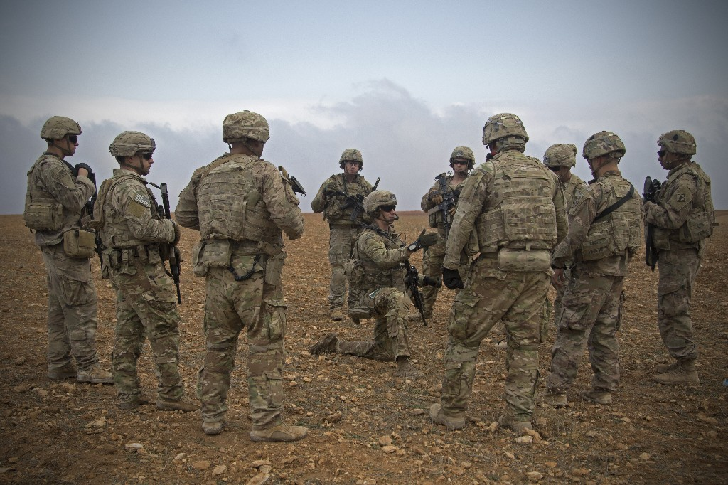 In this Nov. 7, 2018, photo released by the U.S. Army, U.S. soldiers gather for a brief during a combined joint patrol rehearsal in Manbij, Syria. The United States' main ally in Syria on Thursday, Dec. 20, 2018, rejected President Donald Trump's claim that Islamic State militants have been defeated and warned that the withdrawal of American troops would lead to a resurgence of the extremist group. (U.S. Army photo by Spc. Zoe Garbarino via AP)