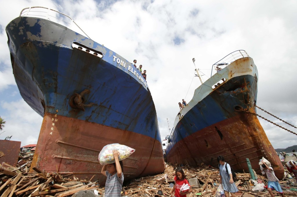 Survivors pass by two large ships after they were washed ashore by strong waves caused by Typhoon Haiyan in Tacloban. AP Photo/Aaron Favila
