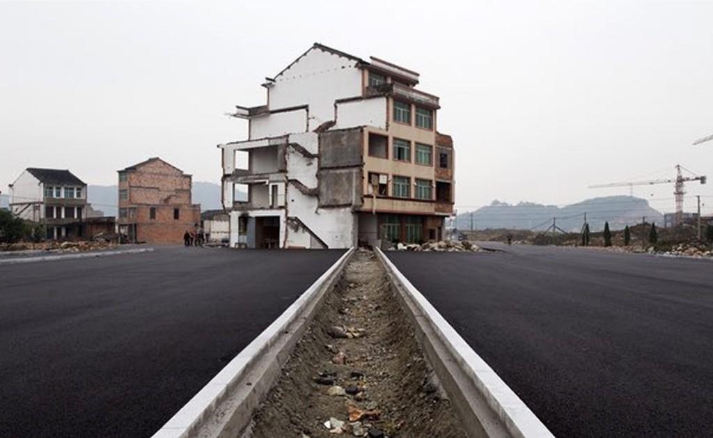 """( 温岭新铺的大路中间一座被推倒一半的""""钉子户""""。户主是一对年过六旬的夫妇。虽然抗争了四年,他们的房子也终究没能幸免。)"""