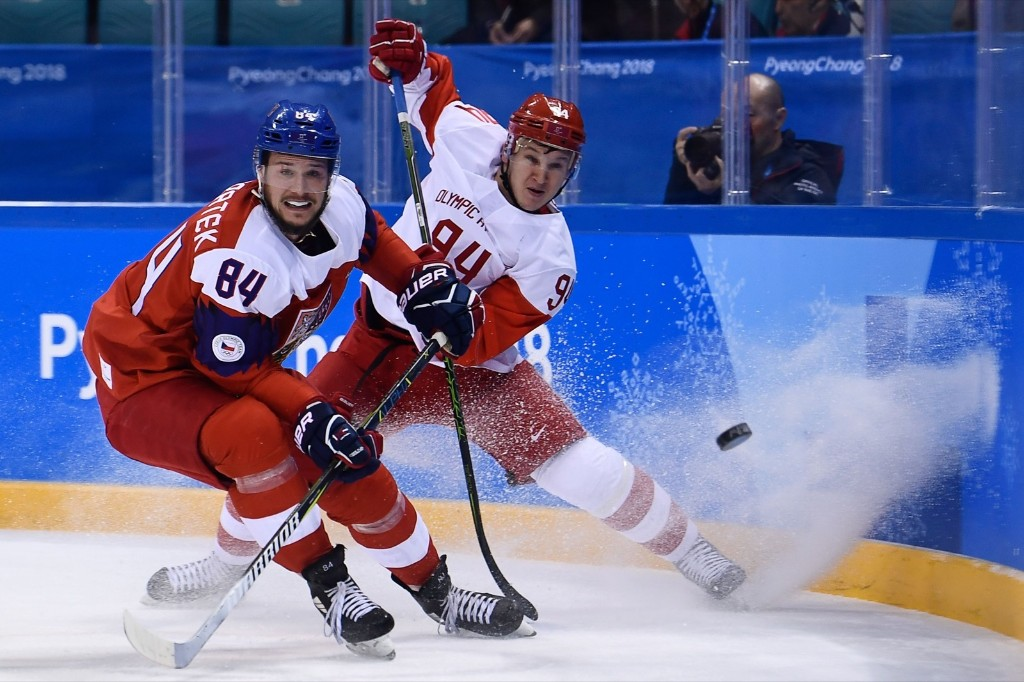 Czech Republic's Tomas Kundratek (L) and Russia's Alexander Barabanov fight for the puck. BRENDAN SMIALOWSKI/AFP/Getty Images