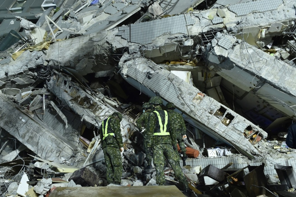Military personnel conduct rescue work at the site of a collapsed building. The powerful earthquake felled a 17-story apartment complex full of families who had gathered for Lunar New Year celebrations. SAM YEH/AFP/Getty Images