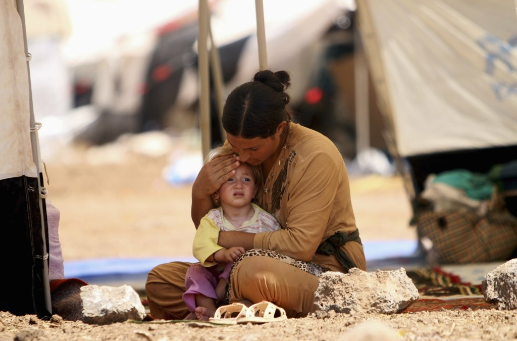 A Yazidi woman, who fled the violence in the Iraqi town of Sinjar, inside a tent at Nowruz refugee camp in Qamishli, Syria. REUTERS/Rodi Said