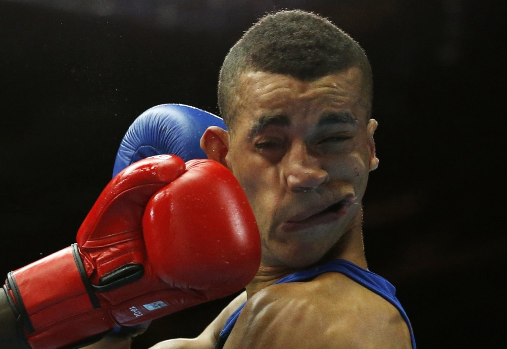 Kenya's Denis Okoth lands a punch on England's Samuel Maxwell during bout at the Commonwealth Games. REUTERS/Jim Young
