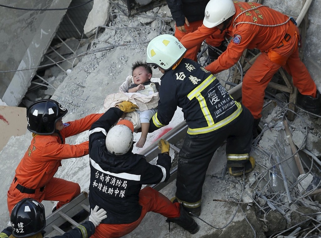 Rescue personnel help a child rescued at the site where a 17-story apartment building collapsed. REUTERS/Stringer