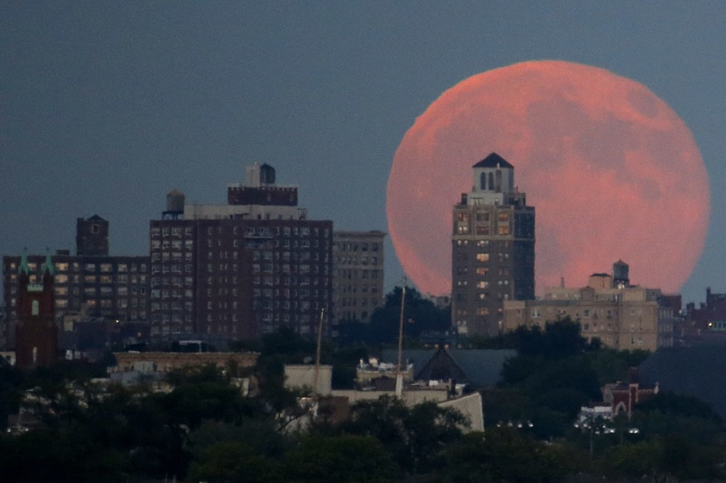 A blue moon rises behind Brooklyn as seen from Liberty State Park in Jersey City, N.J. AP Photo/Julio Cortez