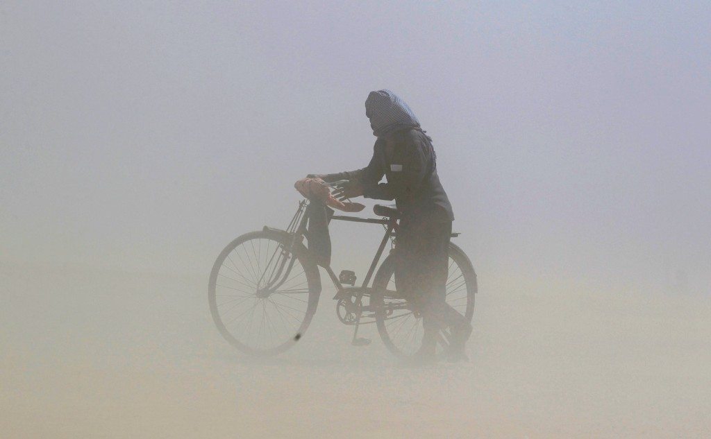 A man pushes a bicycle through a dust storm on the banks of the Ganga river in Allahabad, India. REUTERS/Jitendra Prakash