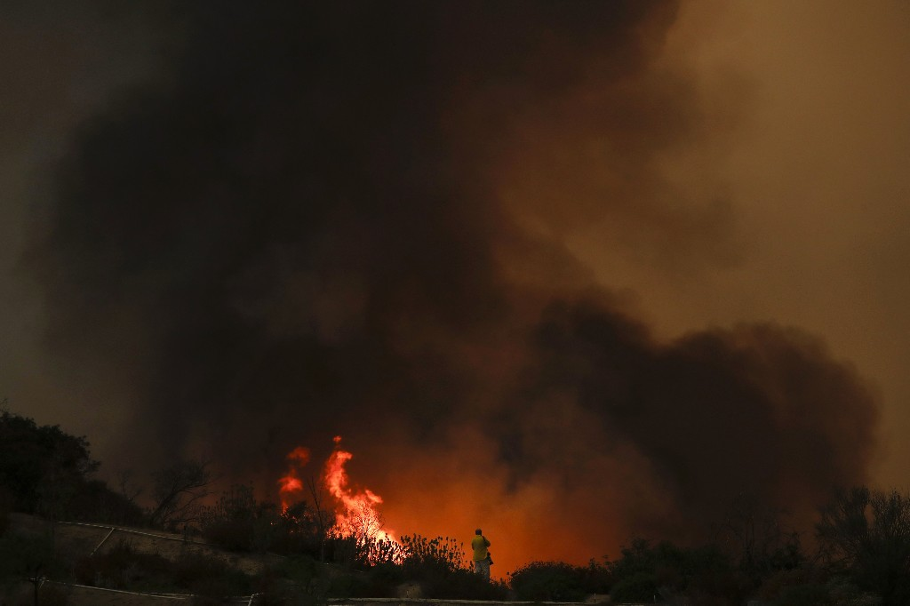 A photographer takes pictures of a wildfire burning near a residential area Wednesday, Aug. 8, 2018, in Lake Elsinore, Calif. The flames gained renewed strength Wednesday, sending up thick smoke that officials say is creating unhealthy conditions in some neighborhoods. (AP Photo/Jae C. Hong)