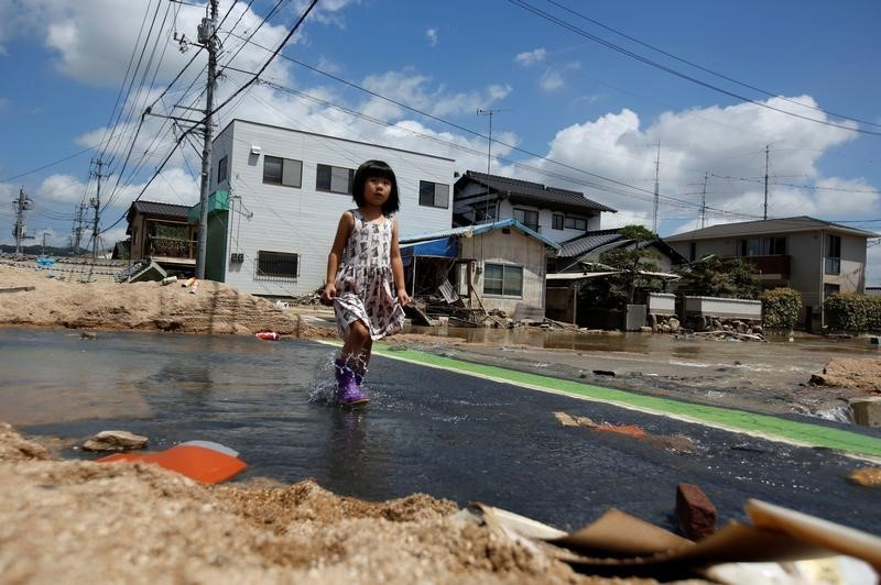 A local resident walks in a flood affected area in Mabi town in Kurashiki, Okayama Prefecture, Japan, July 10, 2018. REUTERS/Issei Kato