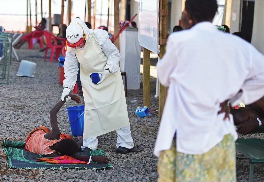 A health worker assists an Ebola patient at the Kenama treatment centre in Sierra Leone. FRANCISCO LEONG/AFP/Getty Images