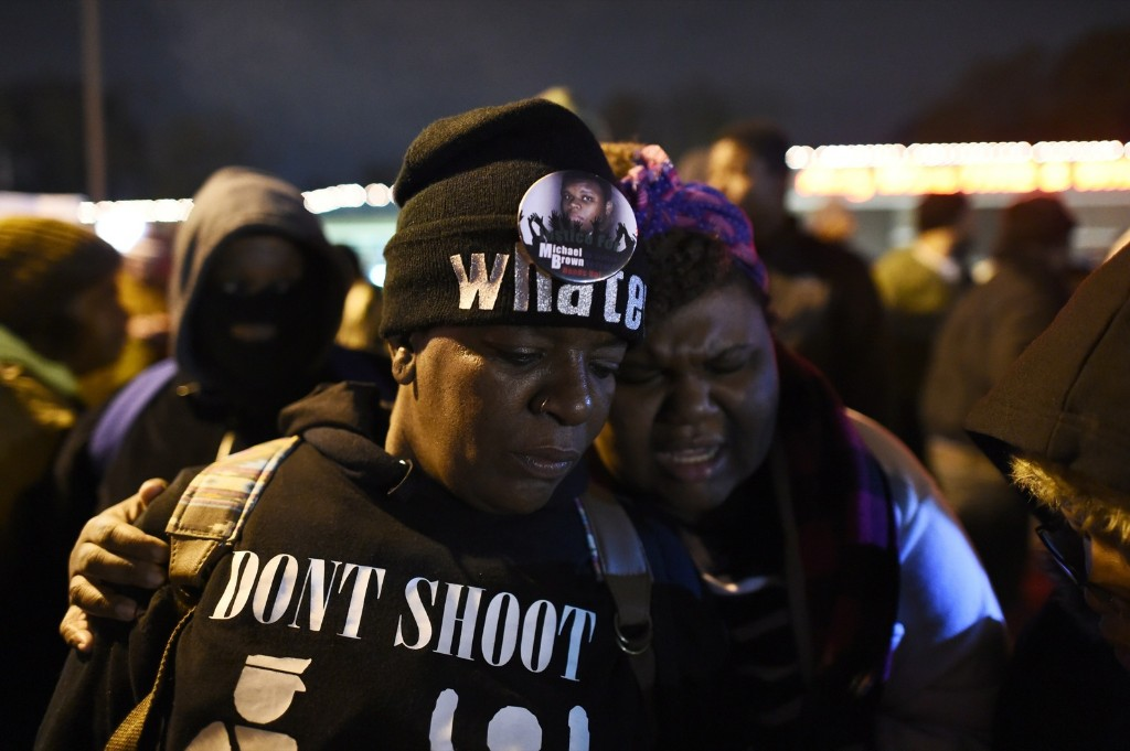 A group of demonstrators pray in front of the police station in Ferguson. JEWEL SAMAD/AFP/Getty Images
