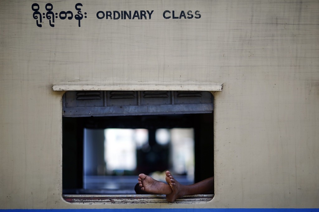 A man sleeps inside a train parked at a station in Naypyitaw, Myanmar. REUTERS/Damir Sagolj