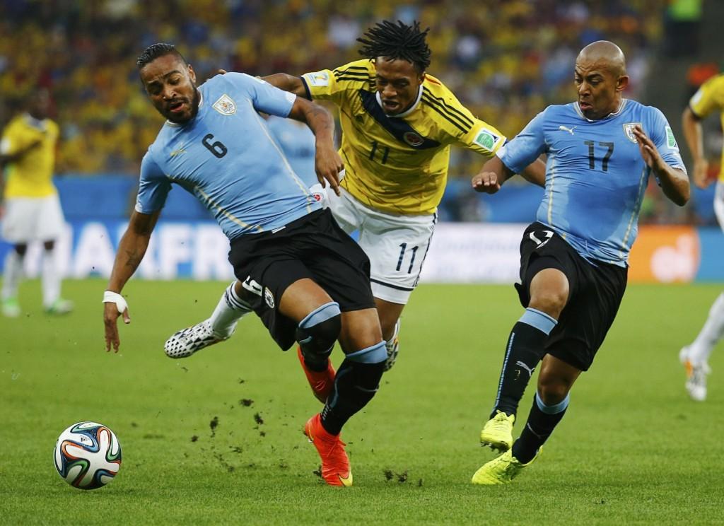 Colombia's Juan Cuadrado fights for ball with Uruguay's Alvaro Pereira and Egidio Arevalo Rios. REUTERS/Kai Pfaffenbach