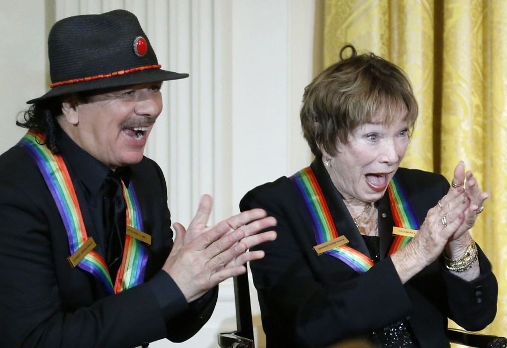 Kennedy Center Honors recipients Carlos Santana and Shirley MacLaine laugh at a joke by President Barack Obama. REUTERS/Jonathan Ernst