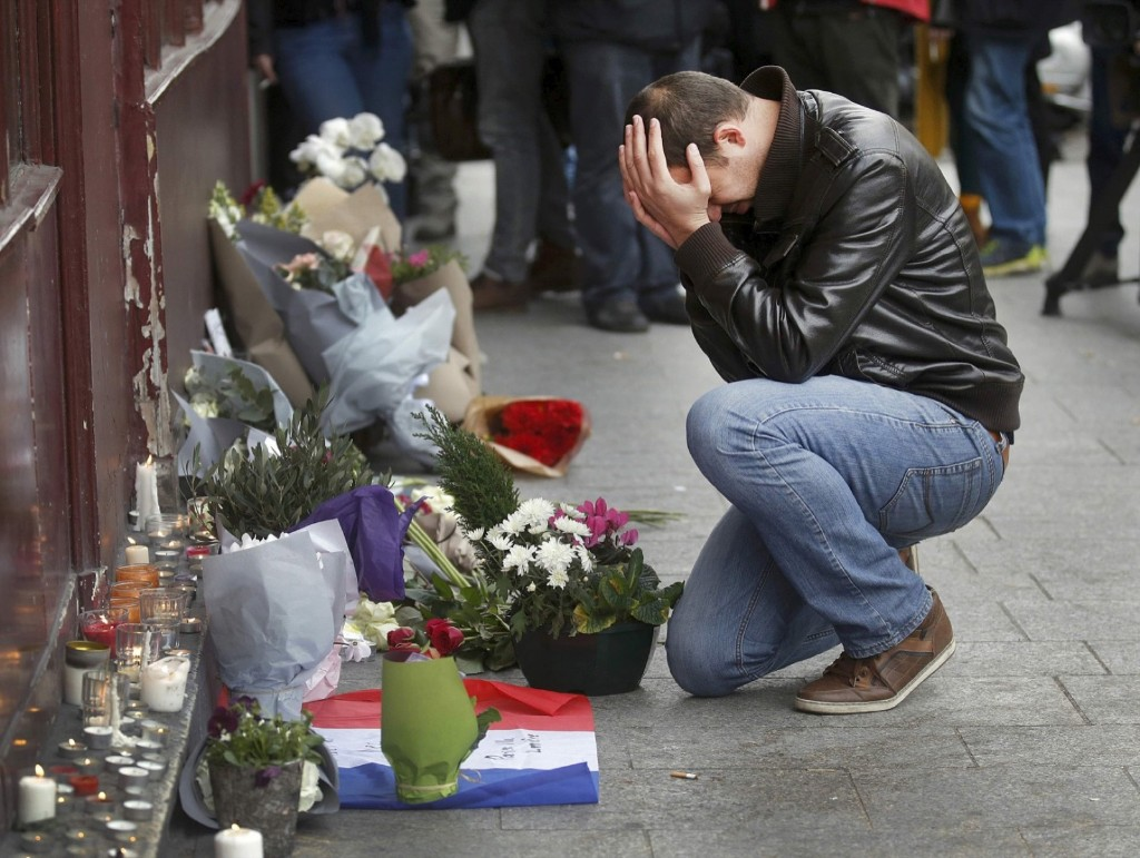 A man pays his respect outside Le Carillon restaurant the morning after a series of deadly attacks in Paris. REUTERS/Christian Hartman
