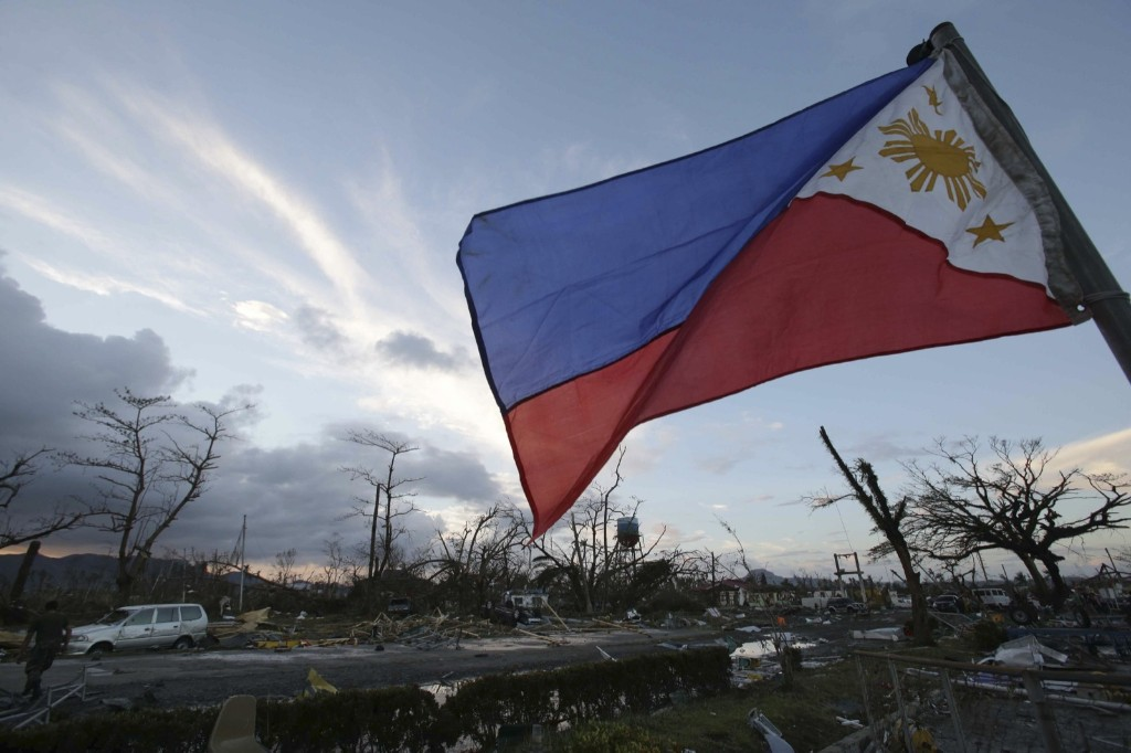A Philippine flag stands amongst the damage caused by powerful Typhoon Haiyan. AP Photo/Aaron Favila