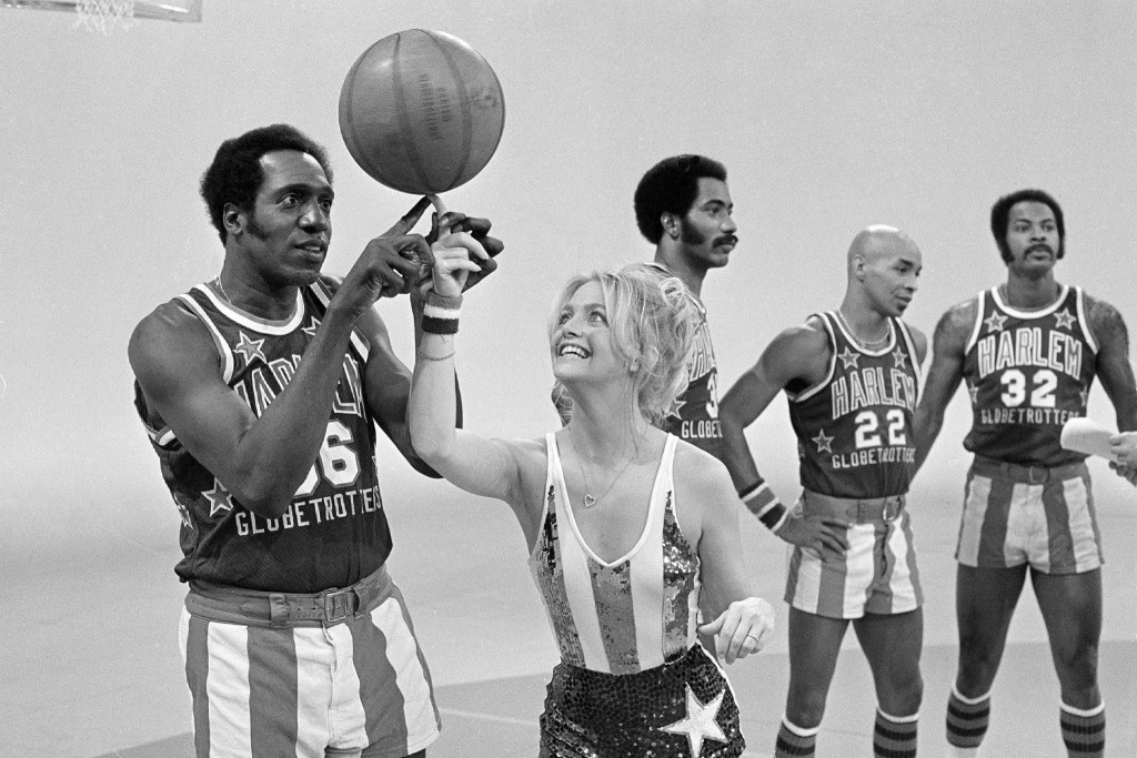 Actress Goldie Hawn has her finger guided to the basketball by Harlem Globetrotters Meadowlark Lemon during the taping of her CBS special, 1978. AP Photo/Jeff Robbins