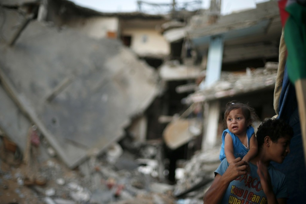 A Palestinian boy holds his sister near the ruins of their family's house east of Gaza City. REUTERS/Suhaib Salem