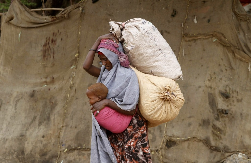 A displaced Somali woman carries a child and her belongings after fleeing famine, near Mogadishu. REUTERS/Feisal Omar