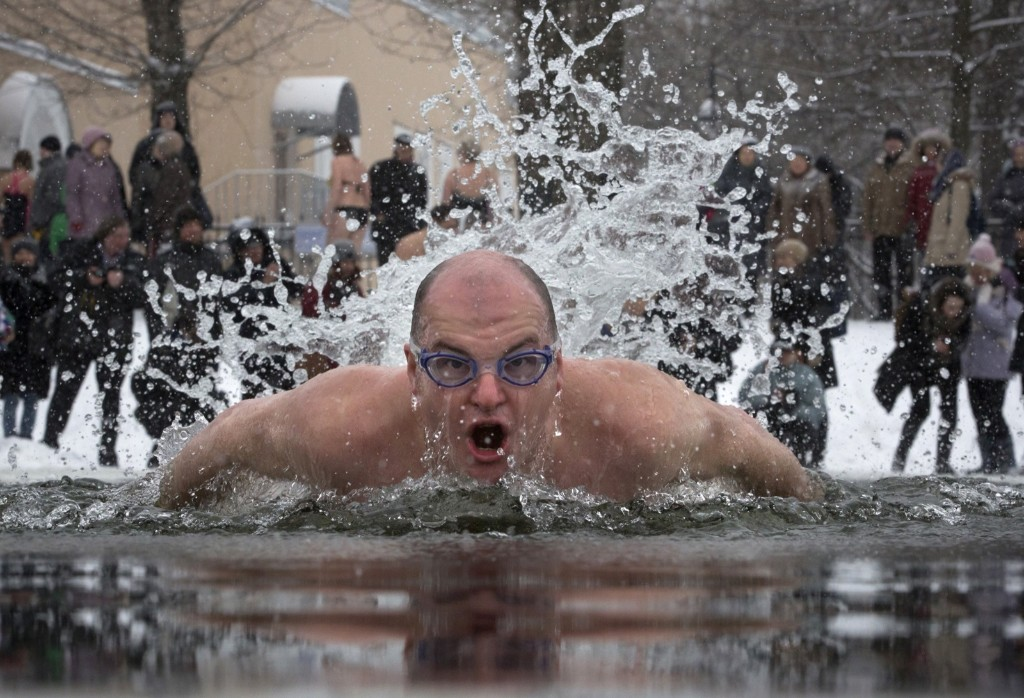 A Russian man swims in icy water marking the 71st anniversary of the breaking the Nazi siege of Leningrad during WWII, in St. Petersburg. AP Photo/Dmitry Lovetsky