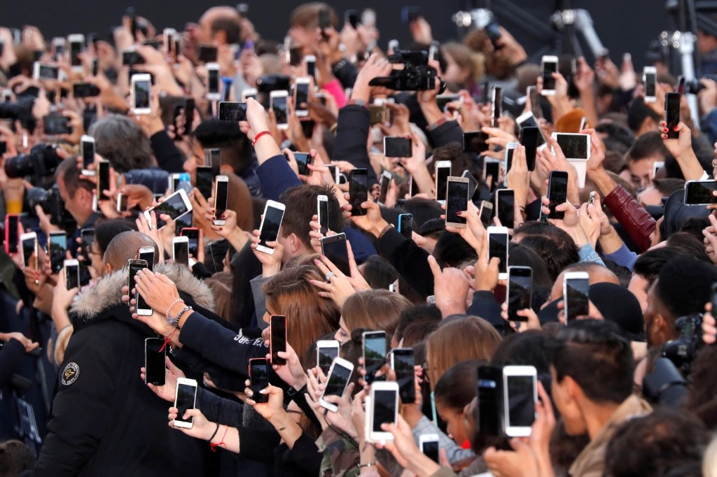 People use their smartphone to take photos of the L'Oreal fashion show on the Champs Elysees during a public event organized by the French cosmetics group as part of Paris Fashion Week. REUTERS/Charles Platiau