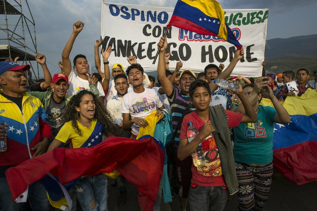 """Government supporters chant anti-U.S. slogans during the first day of the """"Hands off Venezuela"""" three-day music festival at the Tienditas International Bridge, in Urena, Venezuela, Friday, Feb. 22, 2019, on the border with Colombia. Venezuela's power struggle is set to convert into a battle of the bands Friday when musicians demanding Nicolas Maduro allow in humanitarian aid and those supporting the embattled leader's refusal sing in rival concerts being held at both sides of a border bridge where tons of donated food and medicine are being stored. (AP Photo/Rodrigo Abd)"""