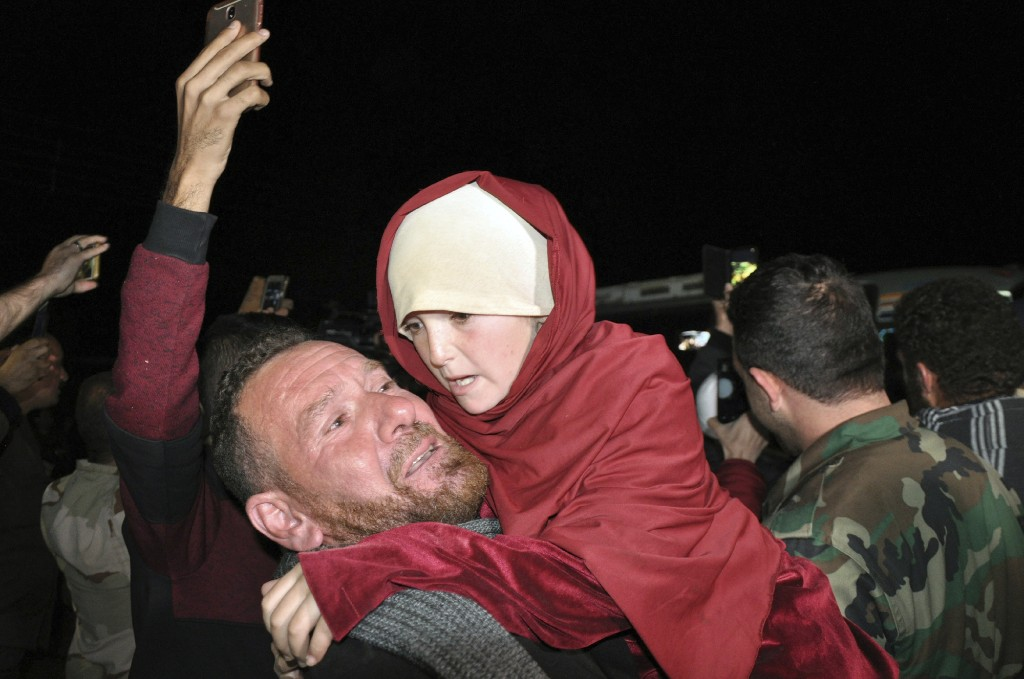 In this photo released by the Syrian official news agency SANA, a man holds an young girl who has been rescued from the Islamic State group in the Hamima area east of the historic town of Palmyra, after she arrived with others liberated hostages to the southern province of Sweida, Syria, Friday, Nov. 9, 2018. Islamic State group militants shot and killed two children during an operation to liberate a group of hostages from southern Syria that were being held by the extremist group since July, a father and activists said Friday. (SANA via AP)