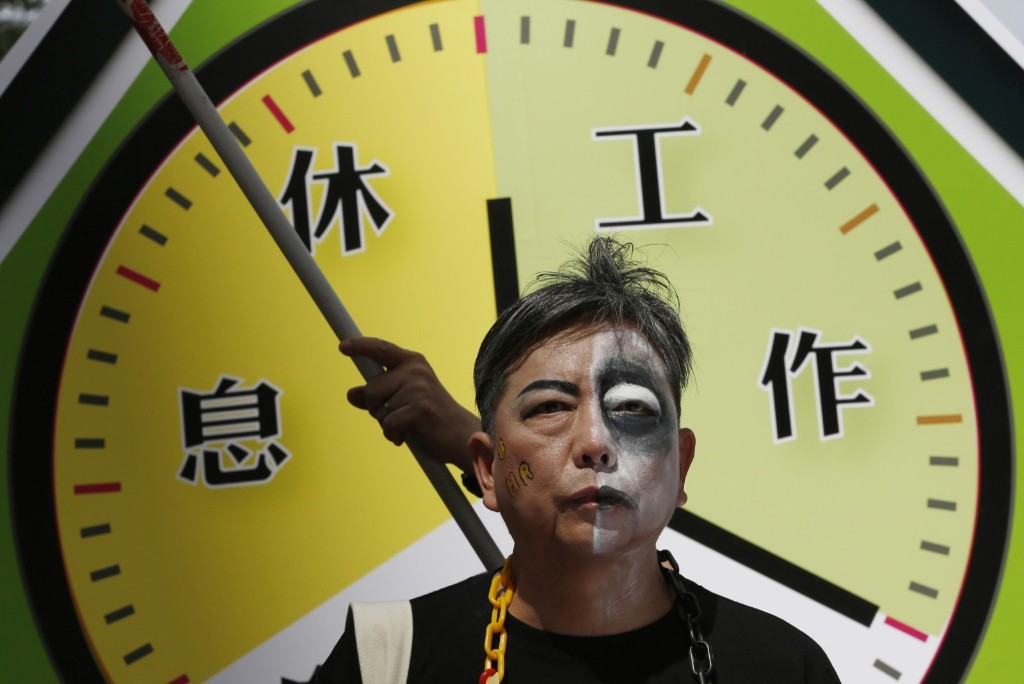 A protester with half his face painted as zombie in front of a mock clock during a May Day march in Hong Kong. AP Photo/Kin Cheung