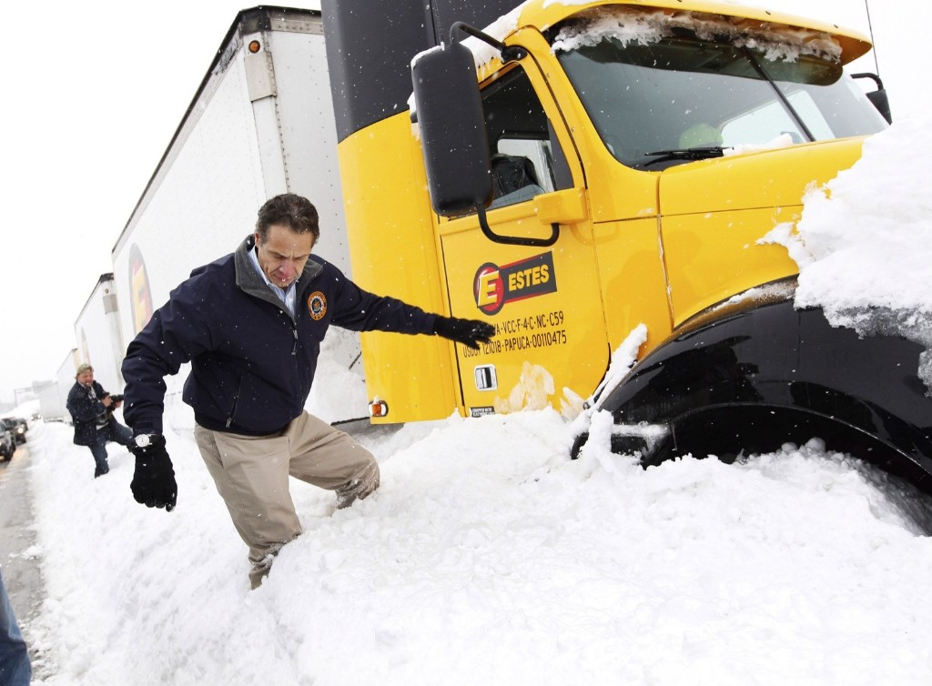 New York Governor Andrew Cuomo climbs over snow piled on the highway after talking with a stranded trucker on interstate I-190 in West Seneca, New York Wednesday. REUTERS/Sharon Cantillon/Buffalo News