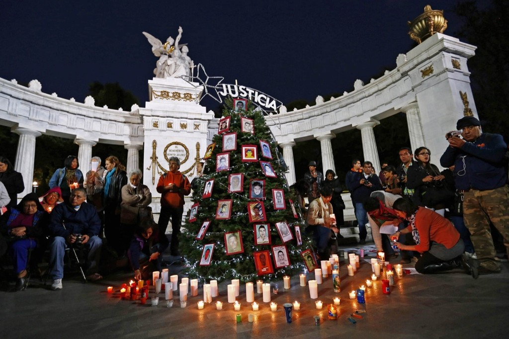 Activists next to a Christmas tree with photos of the missing students from Ayotzinapa Teacher Training College Raul Isidro Burgos at Hemiciclo de Juarez monument in Mexico City. REUTERS/Edgard Garrido