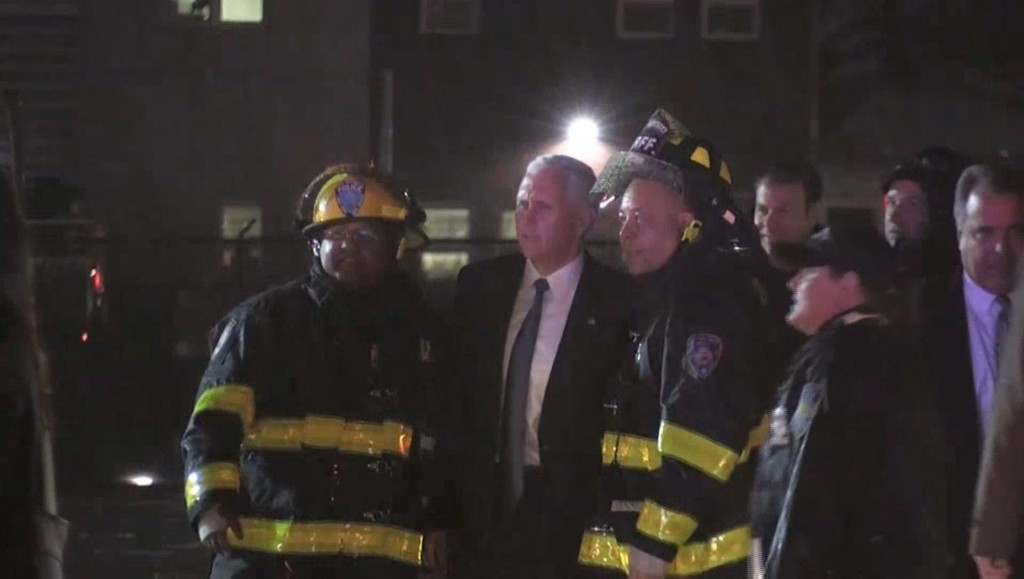 Mike Pence with firefighters after a plane carrying him skidded off the runway after landing in the rain at New York City's LaGuardia Airport. US TV POOL via Reuters TV