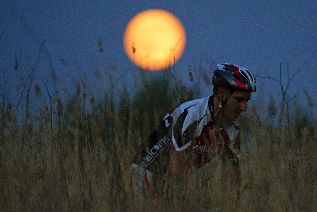A cyclist rides his mountain bike as the Blue Moon rises in a park in Rome. REUTERS/Max Rossi
