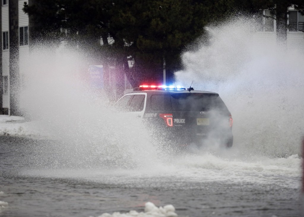 An Atlantic City police officer drives through a flooded street early Saturday. AP Photo/Mel Evans