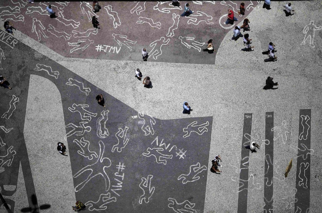 People walk over drawings depicting chalk outlines of bodies during a protest at Carioca square in downtown Rio de Janeiro, Tuesday. The drawings represent the 4,000 victims of violence who died in Rio in 2012. REUTERS/Ricardo Moraes