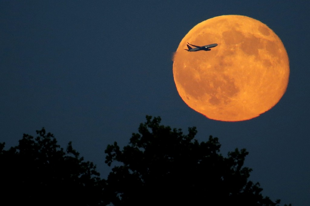 A plane ascends in front of a blue moon rising as seen from Liberty State Park in Jersey City, N.J. AP Photo/Julio Cortez
