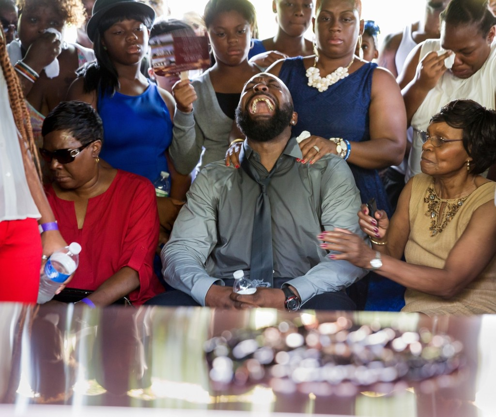 Michael Brown Sr. yells out as the casket is lowered into the ground during funeral for his son Michael. Richard Perry/Pool