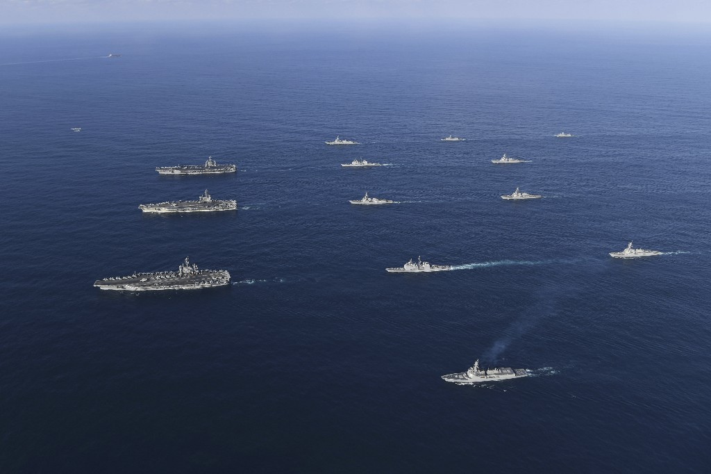 FILE - In this Nov. 12, 2017, file photo provided by South Korea Defense Ministry, three U.S. aircraft carriers USS Nimitz, left top, USS Ronald Reagan, left center, and USS Theodore Roosevelt, left bottom, participate with other U.S. and South Korean navy ships during the joint naval exercises between the United States and South Korea in waters off South Korea's eastern coast in South Korea. Ahead of the second summit between U.S. President Donald Trump and North Korean leader Kim Jong Un, some observers say there is an uncertainty over the future of the decades-long military alliance between Washington and Seoul. (South Korea Defense Ministry via AP, File)