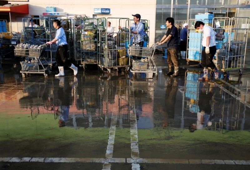 Employees of a supermarket push trolleys and shelves, with muddy items, at their store in a flooded area in Mabi town in Kurashiki, Okayama Prefecture, Japan, July 9, 2018. REUTERS/Issei Kato