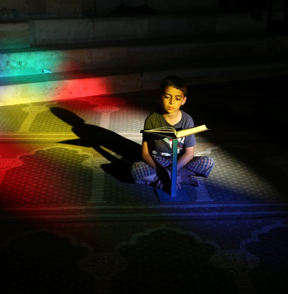 A Palestinian boy reads the Quran in the Al-Omari mosque in Gaza City, June 29. AP Photo/Hatem Moussa