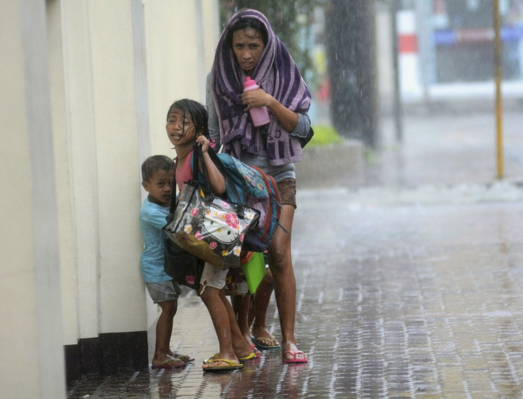 A mother takes refuge with her children as Typhoon Haiyan hits Cebu city, central Philippines. Haiyan, a category-5 super typhoon, bore down on the northern tip of Cebu Province, a popular tourist destination. REUTERS/Zander Casas