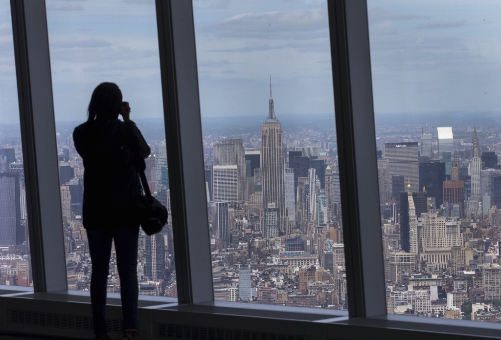 A woman photographs the Manhattan skyline from the One World Observatory on the 100th floor of the One World Trade Center tower in New York, Wednesday. REUTERS/Mike Segar