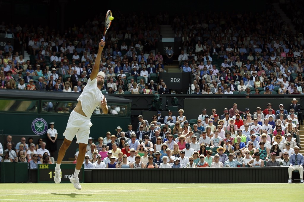 Ivo Karlovic serves to Andy Murray. AP Photo/Alastair Grant