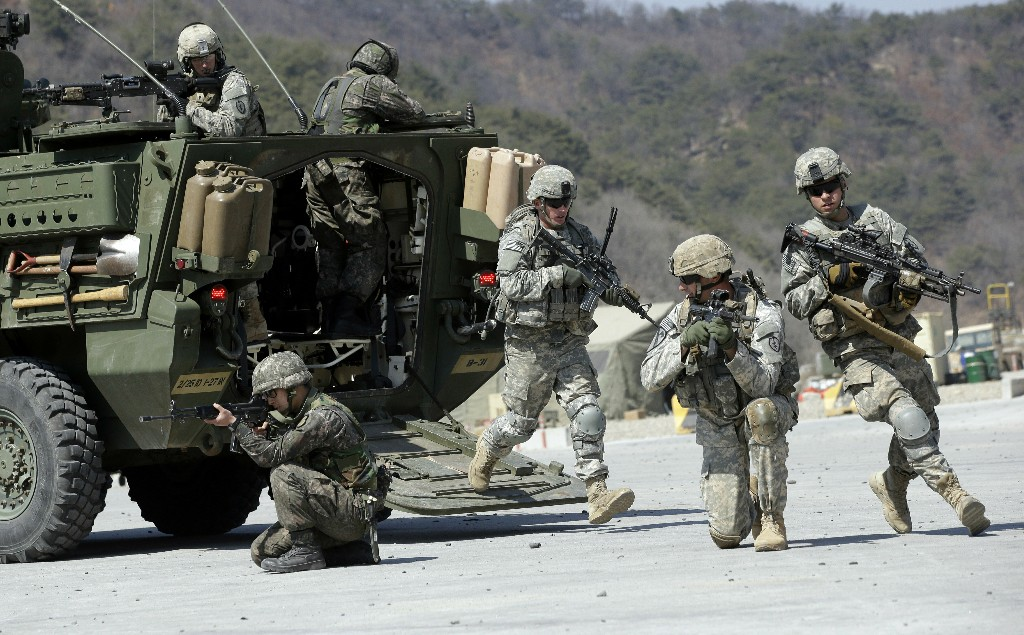 FILE - In this March 25, 2015, file photo, U.S. Army soldiers from the 25th Infantry Division's 2nd Stryker Brigade Combat Team and South Korean soldiers take their position during a demonstration of the combined arms live-fire exercise as a part of the annual joint military exercise Foal Eagle between South Korea and the United States at the Rodriquez Multi-Purpose Range Complex in Pocheon, South Korea. Ahead of the second summit between U.S. President Donald Trump and North Korean leader Kim Jong Un, some observers say there is an uncertainty over the future of the decades-long military alliance between Washington and Seoul. (AP Photo/Lee Jin-man, File)